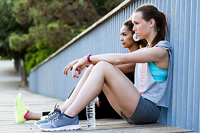 Two sporty young women relaxing on a bridge after workout - p300m2132049 by Josep Suria