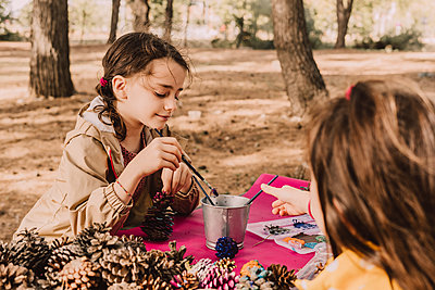 Cute sisters coloring while sitting with pine cones at picnic table in park - p300m2225502 by Eloisa Ramos