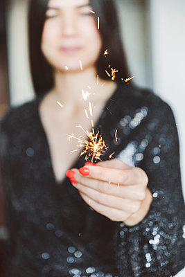 Woman wearing glittering dress holding sparkler while standing at home - p300m2242813 by Ekaterina Yakunina