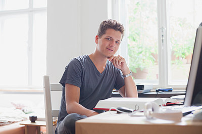 Portrait of handsome young male university student studying at home - p301m1498681 by Larry Washburn