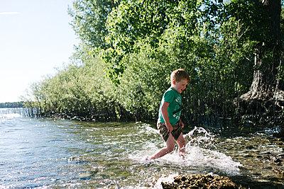 Boy running in water, Kingston, Canada - p429m2019338 by Viara Mileva