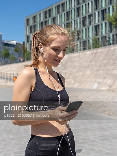 Young athletic woman uses smartphone with earphones - p1332m2183857 by Tamboly