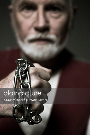 Old, bearded man with metal chain wrapped around his fist. - p1433m1586214 by Wolf Kettler