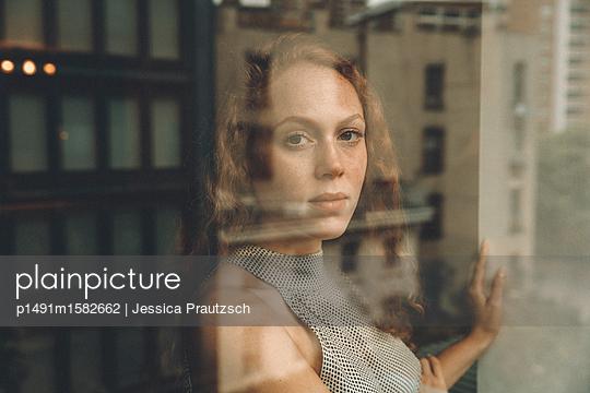 Frau schaut durch Fenster - p1491m1582662 von Jessica Prautzsch