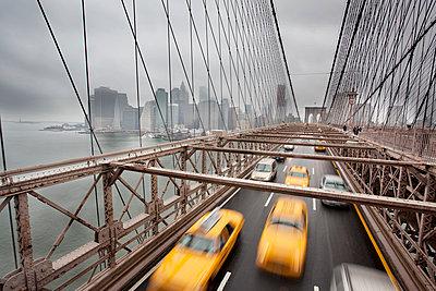 Blurred yellow taxis on Brooklyn bridge at New York City, USA - p1025m788823f by Nicklas Blom