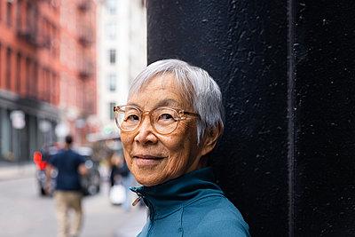 Smiling senior woman wearing eyeglasses standing by black wall - p1166m2285623 by Cavan Images