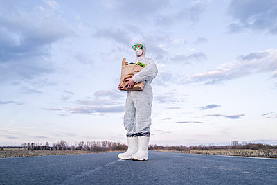 Man wearing protective suit and mask holding grocery bag on a country road - p300m2170787 by Ekaterina Yakunina