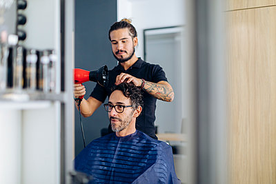 Hairdresser blow drying man's hair at salon - p300m2203037 by Sofie Delauw