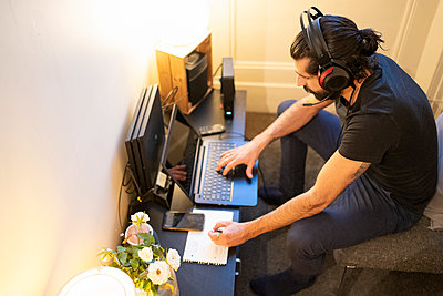 Male entrepreneur writing in note pad while using laptop at home - p300m2274364 by Francesco Buttitta