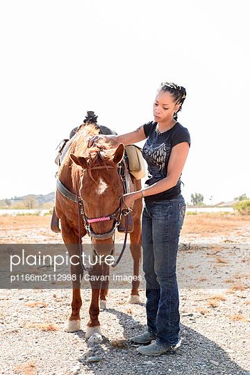 Woman standing by brown horse on dirt road against clear sky during sunny day - p1166m2112998 by Cavan Images