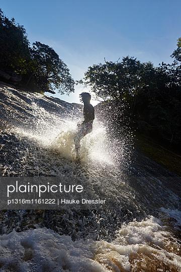 Wasserfall-Surfer, Steinrutsche, des Flusses Rio Ribeirao do Meio, Männer aus dem Dorf rutschen stehend auf Fusssohlen, bei Lencois, Hauptort, Ausgangspunkt fuer Chapada Diamantina National Park, Bahia, Brasilien - p1316m1161222 von Hauke Dressler