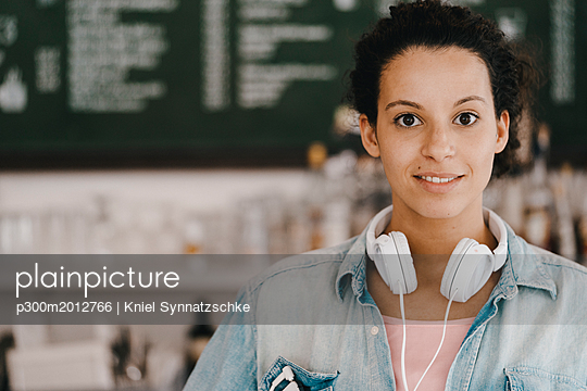 Young woman with headphones, working in coworking space - p300m2012766 von Kniel Synnatzschke