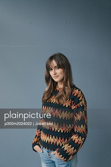 Pretty woman against gray background, with hands in pockets - p300m2024022 von Joseffson