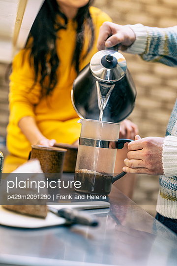 Hipster couple having coffee and talking in kitchen - p429m2091290 by Frank and Helena