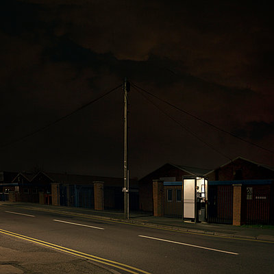 Person In Telephone Box at night - p1072m1056679 by Aaron Sehmar