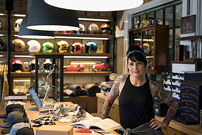 Portrait confident female motorcycle mechanic behind shop counter - p1192m1447371 by Hero Images