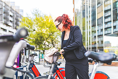 Red haired businesswoman unlocking hire bicycle outside city office - p429m1448061 by William Perugini