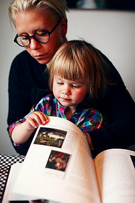 Mother and daughter leafing through book - p972m1088624 by Felix Odell