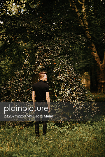 Young man standing at the edge of the forest - p1267m2259749 by Jörg Meier