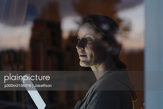 Woman looking out of window in twilight, holding digital tablet - p300m2156316 by Joseffson