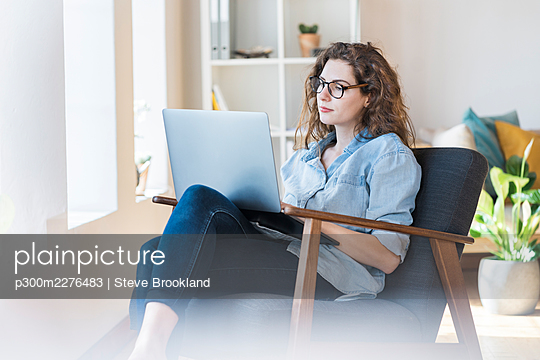 Woman using laptop while sitting on armchair in living room - p300m2276483 by Steve Brookland