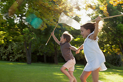 Happy boy and girl holding hands and running with butterfly nets in grass - p1023m756147f by Sam Edwards