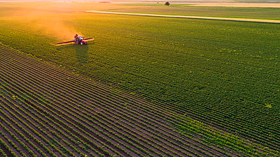 Serbia, Vojvodina, Aerial view of a tractor spraying soybean crops - p300m2069604 by oticki