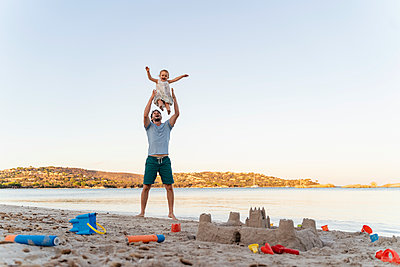 Sand castle and happy father lifting up daughter on the beach - p300m2143496 by Daniel Ingold