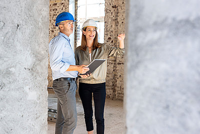 Female client gesturing while discussing with male architect at construction site - p300m2276151 by Peter Scholl