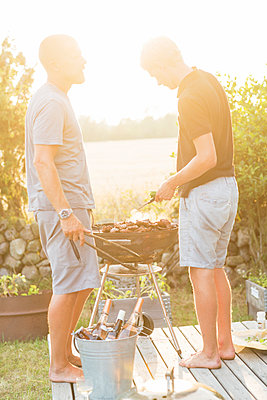 Two men having barbecue - p312m992967f by Ulf Huett Nilsson