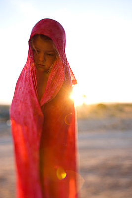 Portrait of little girl with shawl wrapped around her - p343m963724 by Woods Wheatcroft photography