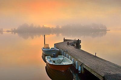 Sweden, Stockholm Archipelago, Uppland, Lidingo, Jetty and anchored boat at foggy dawn - p352m1079591f by Eddie Granlund