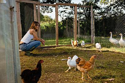 Junge Frau hockt lächelnd im Hühnergehege - p432m2293138 von mia takahara