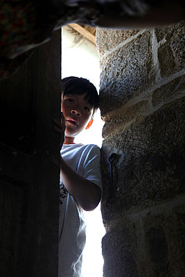 Young boy looking through crack of the door - p664m1169098 by Yom Lam
