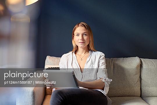 Junge Frau mit Tablet Computer auf dem Sofa - p1124m1589187 von Willing-Holtz