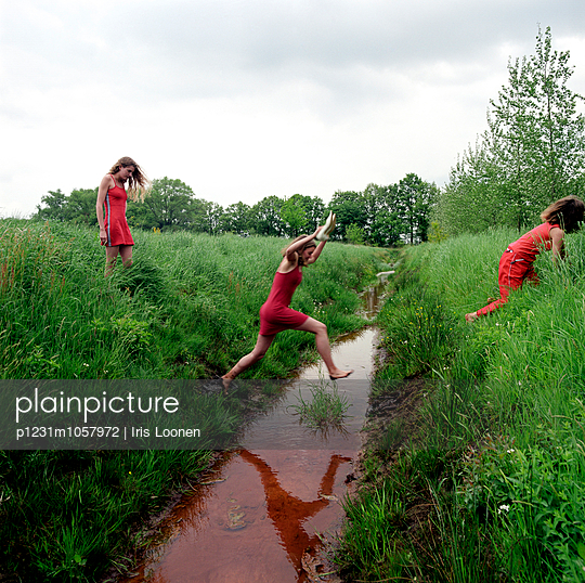 Girls jumping over the ditch - p1231m1057972 by Iris Loonen