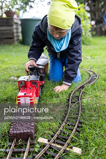 Boy playing with toy train in the garden - p236m2196628 by tranquillium