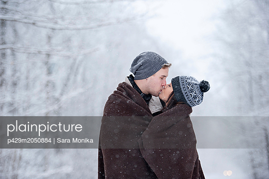 Romantic young couple kissing in snowy forest, Ontario, Canada - p429m2050884 by Sara Monika
