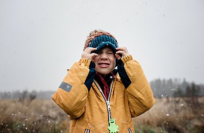 boy covering his face with his hat whilst playing in the snow - p1166m2157411 by Cavan Images