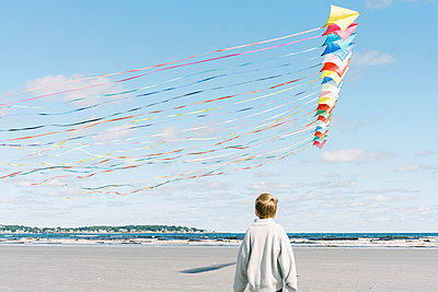A boy admiring a large kite flying past him on a New England beach - p1166m2212926 by Cavan Images