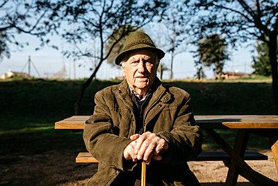 Spain, Barcelona. Retired senior man sitting on park bench leaning on his cane, looking at camera. - p300m2166540 von Josep Rovirosa