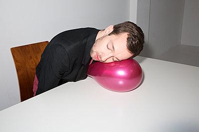 Junger Mann stützt Kopf auf Luftballon - p341m1216622 von Mikesch