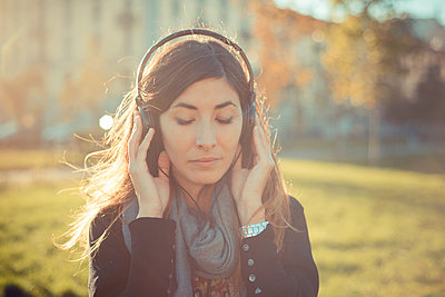 Mid adult woman with eyes closed listening to headphones in park - p429m1013024f by Eugenio Marongiu