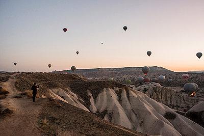 Woman enjoying view and display of hot air balloons in valley, GÌŠreme, Cappadocia, Nevsehir, Turkey - p429m2138568 by Rosanna U