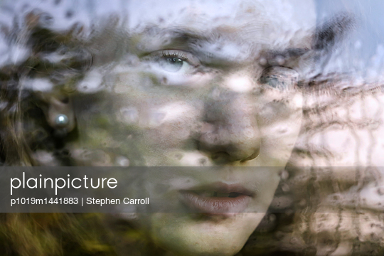 Girl seen through wet car window  - p1019m1441883 by Stephen Carroll