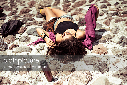 Sorting attractive healthy young tan Mexican sun baking on Stone - p1166m2250645 by Cavan Images