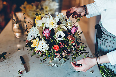 High angle midsection of florist arranging flowers while standing at table in store - p1166m1474278 by Cavan Images