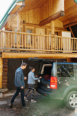 Couple unloading  SUV outside cabin - p1192m2094199 by Hero Images