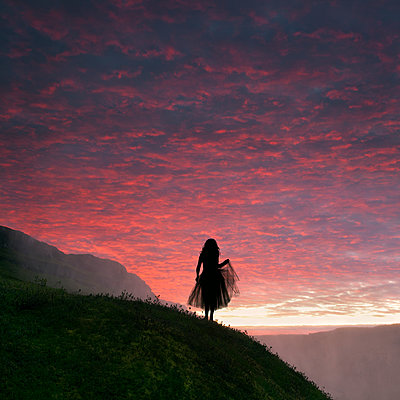 Woman with tulle skirt in front of a dramatic sky in Iceland - p470m2089762 by Ingrid Michel