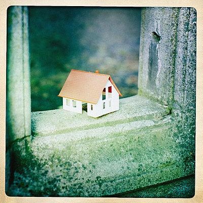 Kleines Modellhaus steht auf verwittertem Stein - p586m962927 von Kniel Synnatzschke